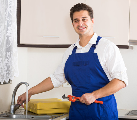 blue overall: Young plumber in blue overall working in domestic kitchen