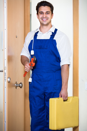 tooling: Happy handyman with tooling at house entrance Stock Photo