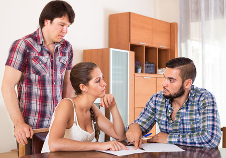 ordinary woman: sad adults signing financial documents at home
