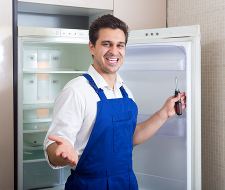 serviceman: adult serviceman fixing technical problems with fridge at residential lot