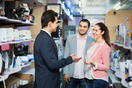 shopping store: Seller and smiling buyers at household appliances section of supermarket Stock Photo