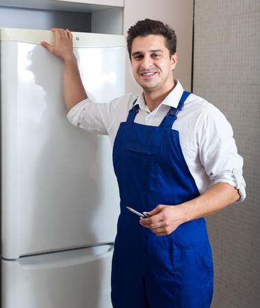 serviceman: portrait of serviceman fixing technical problems with fridge at residential lot Stock Photo
