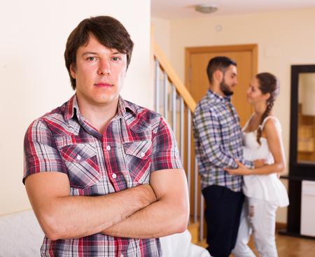 unfaithfulness: Jealous husband watching spouse flirting with friend at home