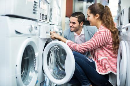 Jong koppel kiezen wasmachine in hypermarkt en glimlachend