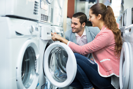 Young couple choosing washing machine in hypermarket and smiling