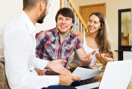 cheerfully: Positive couple and salesman talking cheerfully about purchase at home