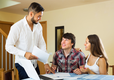 cheerfully: Happy young couple and positive salesman talking cheerfully about purchase at home Stock Photo