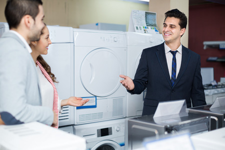 domestic appliances: Positive salesman and adult buyers in store of domestic appliances