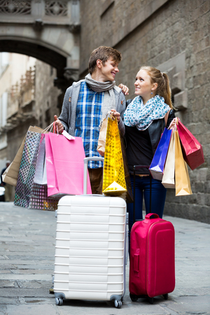 the spouse: Positive spouse walking through European town and carrying shopping bags