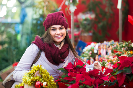 25s: Portrait of female customer 25s choosing eucalyptus decorations for Christmas outdoor Stock Photo