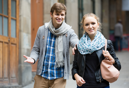 sidewalk talk: Nice-looking  young european male student chasing pleased girl on outdoor date. focus on girl