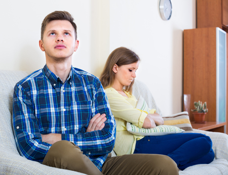 the spouse: Unpleased person criticizing young spouse in living room on sofa