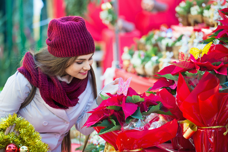 overspending: Pretty young woman buying floral compositions at Christmas market