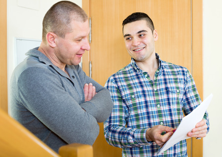 lodger: Young lodger meeting neighbor with papers at doorway. Focus on the right man Stock Photo