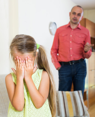 lecturing: Annoyed father lecturing crying mischievous little daughter at home Stock Photo