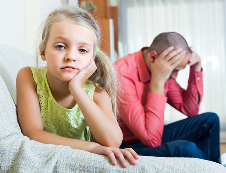 offended: Serious american dad and offended little girl quarrelling indoors. focus on girl Stock Photo