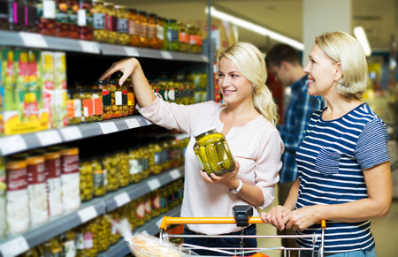 canned goods: Positive women customers standing near shelves with canned goods at store. Focus on the young woman