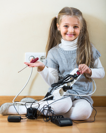 risky: Risky little girl dangerously playing with sockets and electricity alone at home