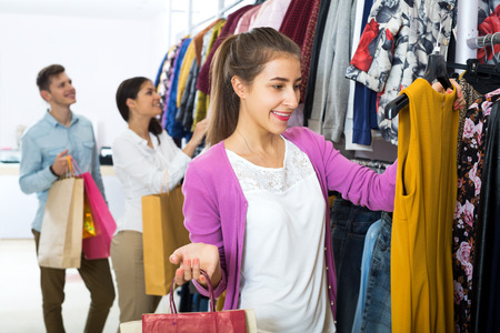 'young things': Attractive young female shopper chooses liked things in the boutique Stock Photo