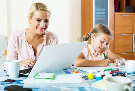 Happy mother with daughter working from home using laptop