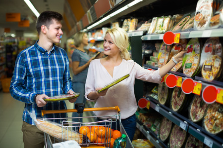 cooled: Happy smiling young couple choosing Italian pizza in cooled food section