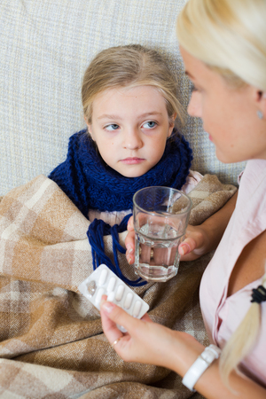 grippe: Little girl with grippe receiving pills from worried mother
