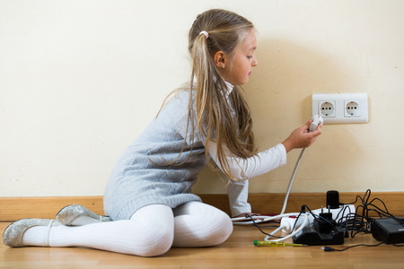 units: Female child with socket extender and charging units indoors