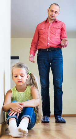 admonition: Annoying dad giving instructions to unhappy frustrated female child at home Stock Photo