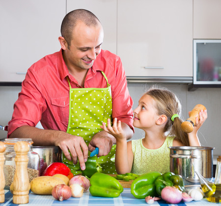 comiendo cereal: Little girl helping father to prepare dinner in kitchen