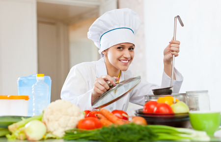 chefs: Portrait of happy female cook in white works with ladle
