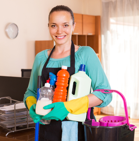 household tasks: Smiling young woman holding detergents and rags in office room