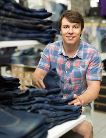 levis: Young smiling american male chooses jeans at clothing store