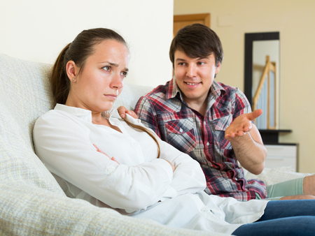 consoling: Man consoling the depressed woman on sofa at a home