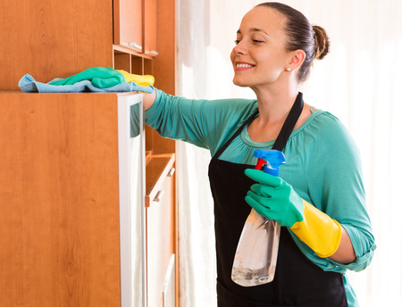 household tasks: Young smiling woman doing cleaning at the office