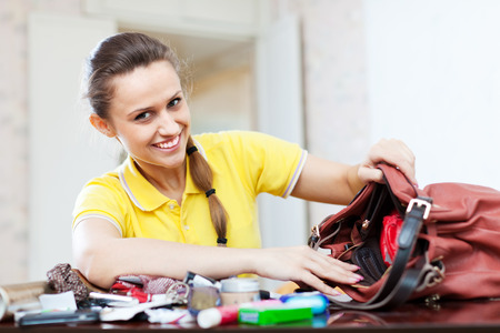 vanity bag: Happy woman lost something and found this thing in handbag Stock Photo