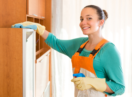 everyday jobs: Positive smiling cleaning woman woman wiping the dust on the shelves at office room