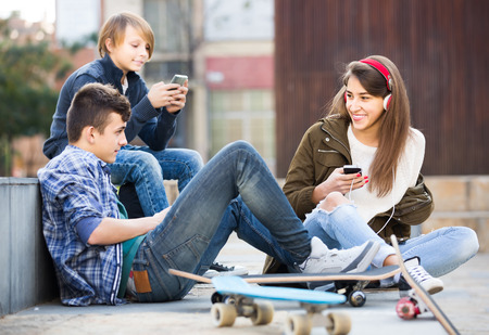 16s: Three happy russian teenagers with smartphones in autumn day outdoors Stock Photo