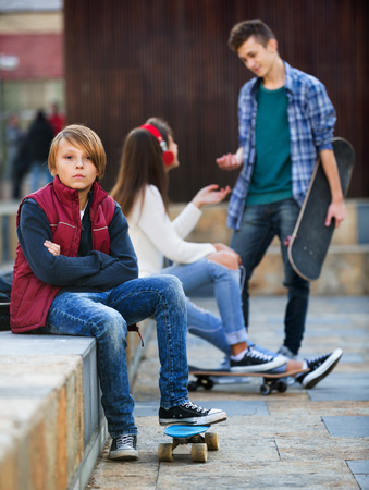 offended: Offended boy and couple of teens apart on the street