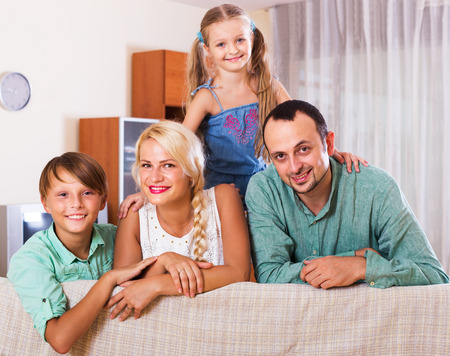 middle class: Portrait of smiling middle class caucasian family with two children at home. Focus on woman Stock Photo