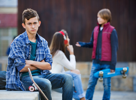16s: Upset boy and happy couple of teens apart on the street
