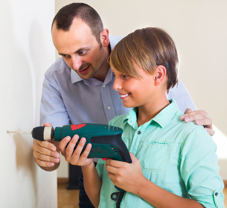 modifying: Happy man teaching son using electric drill at home Stock Photo