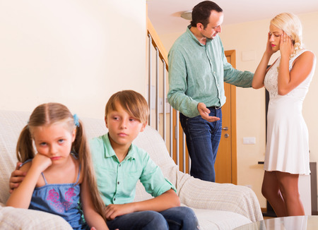 child stress: Unhappy siblings waiting when parents stop screaming indoors