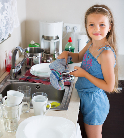 unwashed: Independent little blonde girl doing dishes at kitchen
