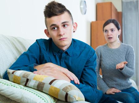 Serious moeder lezingen unpleased tiener in interieur