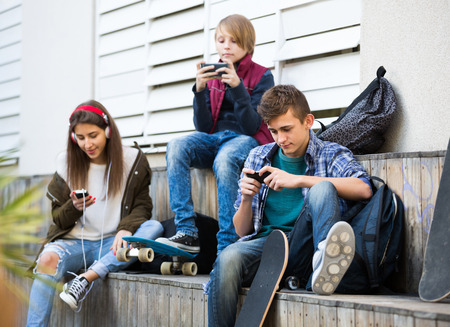 16s: Three teenagers with smartphones in autumn day outside