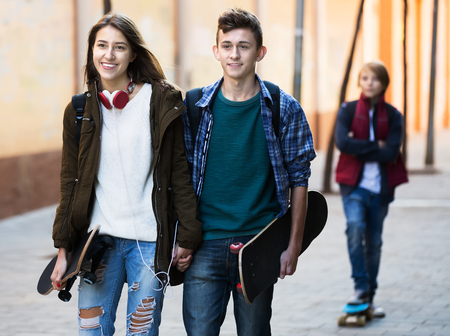16s: Portrait of upset male teen standing aside of girlfriend talking with boy Stock Photo