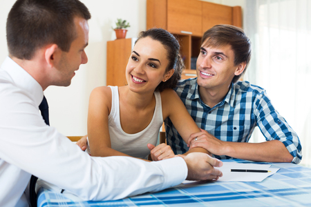 spouses: Confident salesman and young american spouses discussing contract at home Stock Photo