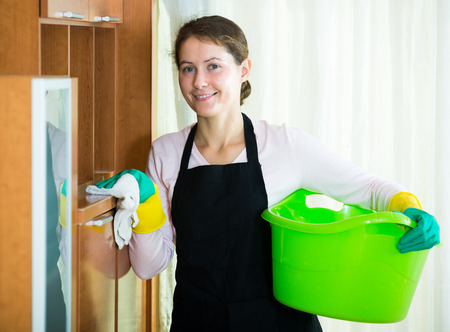 washing clothes: Positive maid in apron dusting and wiping in residential property Stock Photo