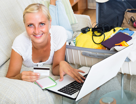 femme valise: Cheerful young blonde using credit card and laptop for planning vacation