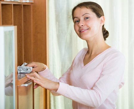 regular people: Cheerful russian woman cleaning at home with smile on face